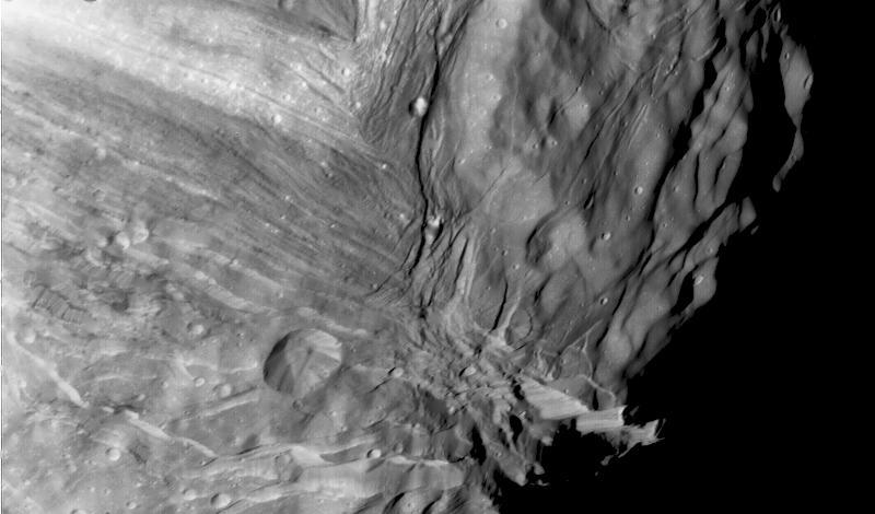 Участок поверхности Миранды, на котором хорошо виден уступ Верона (обрыв высотой 20 км справа внизу). Фотография сделана с аппарата «Вояджер-2» 24 января 1986 года
