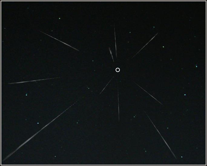 Метеорный поток и его радиант (отмечен окружностью)
