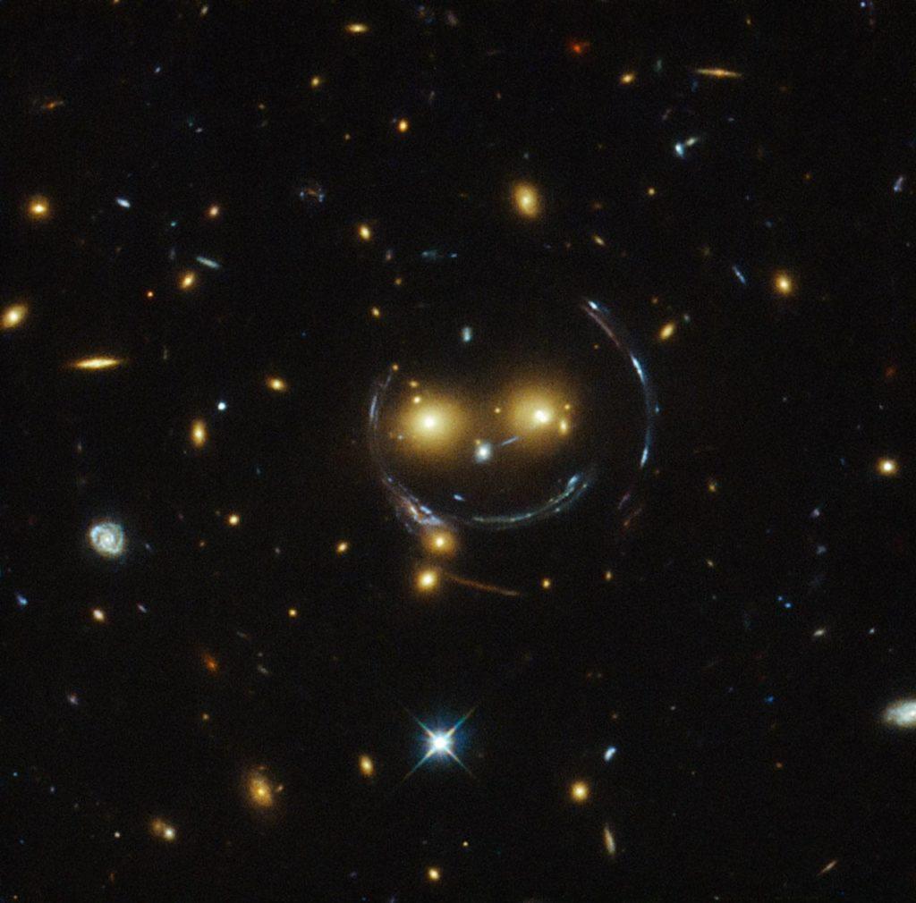 «Смайлик» или «Чеширский Кот»: изображение скопления галактик (SDSS J1038+4849) и результата гравитационного линзирования ими (кольцо Эйнштейна), открытое международной группой исследователей, снимок телескопа Хаббл.